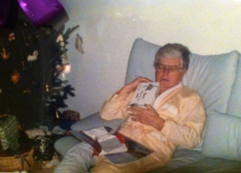 Christmas day priorities: my grandfather... asleep, cradling a box of chocolate...